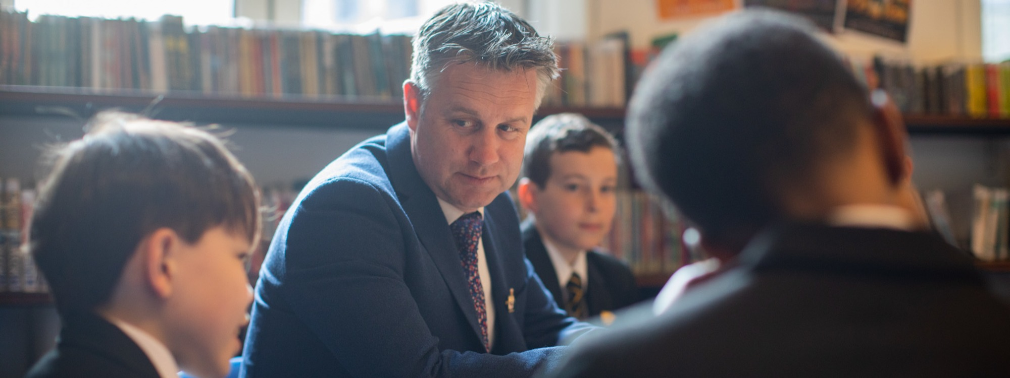 Headteacher with pupils in library